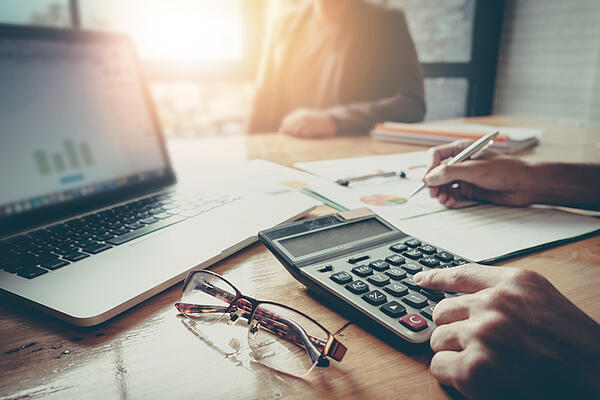 An accountant uses a calculator to calculate a client's tax refund.