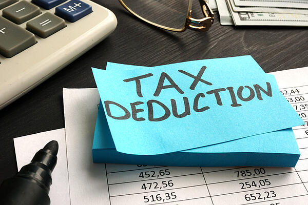 The words tax deduction written on a piece of paper used to calculate business depreciation.