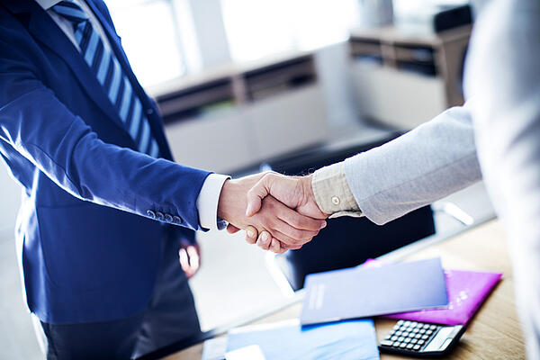 A handshake between a client and an employee of one of the local captive insurance companies.