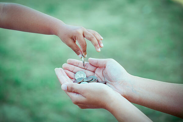 A child places a coin in another person's hand.